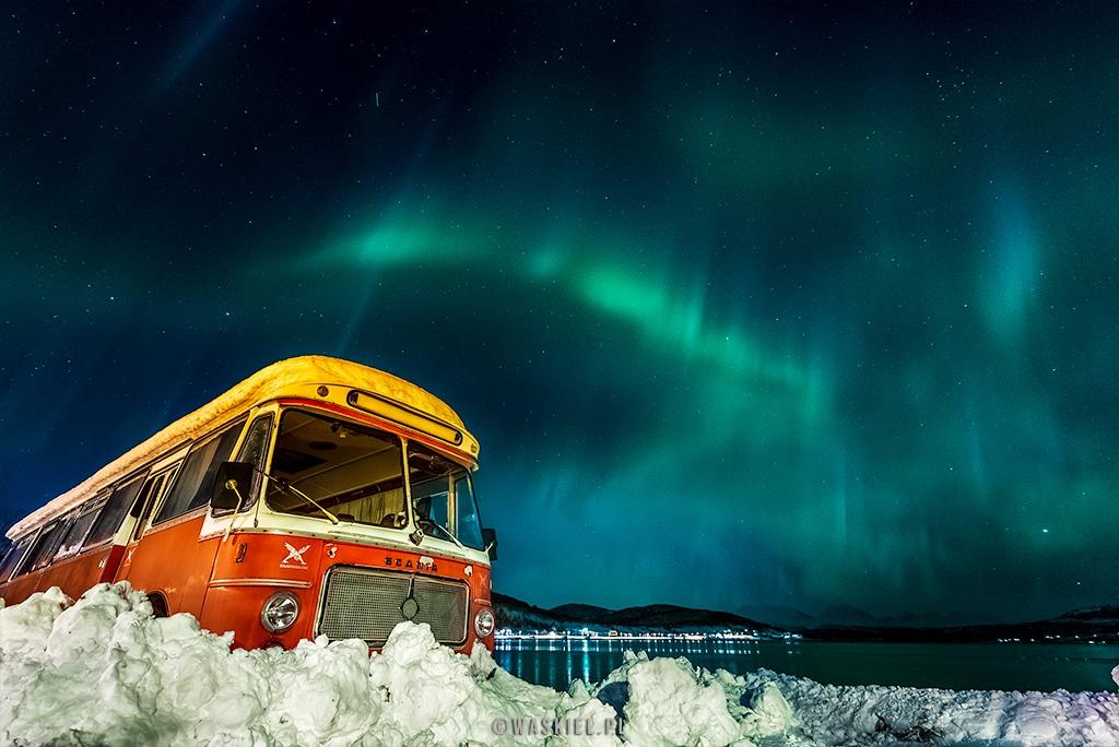 Obraz przedstawiający ciekawe ujęcie zorzy polarnej nad opuszczonym autobusem.