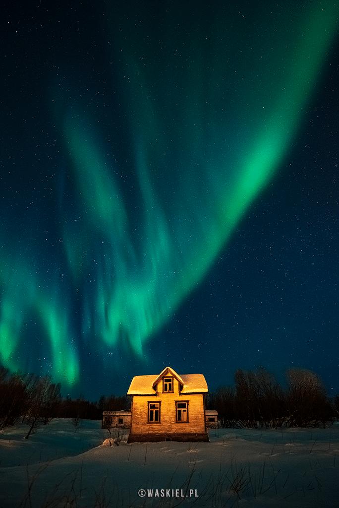 Zdjęcie przedstawiające wygląd zorzy polarnej nad domem jednorodzinnym.